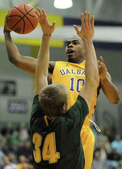UAlbany's Mike Black is guarded by Matt Glass of Vermont as he drives to the basket during a basketb