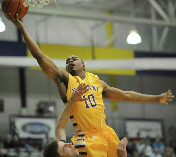 UAlbany's Mike Black is fouled by Matt Glass of Vermont as he drives to the basket during a basketba