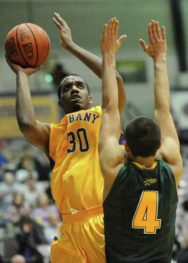 UAlbany's Jayson Guerrier is guarded by Four McGlynn of Vermont as he drives to the basket during a