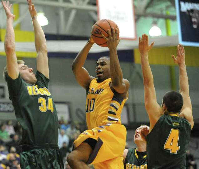 UAlbany's Mike Black drives to the basket during through Vermont's Matt Glass, #34, and Four McGlynn
