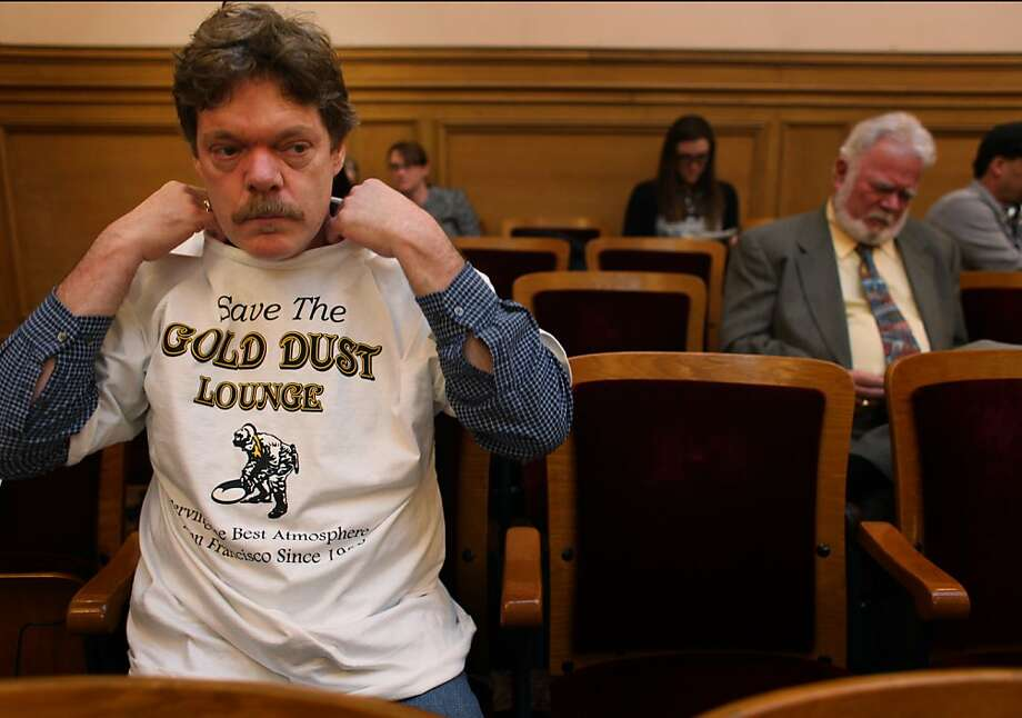 "John Murry, of San Francisco, pulls a ""Save the Gold Dust Lounge"" t-shirt on during a public hearing on the matter at the Historic Preservation Commission in City Hall on Wednesday Feb. 15, 2012 in San Francisco, Calif. With just weeks till an eviction date, advocates hoping to save the Powell Street Bar are trying to make a case that it is a historic landmark. Photo: Mike Kepka, The Chronicle"