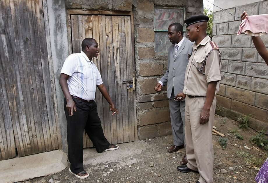 In this photo taken Monday, Feb. 13, 2012, Chief Francis Kariuki, right, accompanied by an assistant, 2nd right, is shown the door where thieves broke into the house of elder Peter Ndungu, left, in the village of Lanet Umoja, near Nakuru, in the Rift Valley of Kenya. Kariuki's latest attempt to improve village life is by using the micro-blogging site Twitter to send a receive information about crime and other local matters, showing that the power of social media has reached even into a dusty African village. Photo: Khalil Senosi, Associated Press