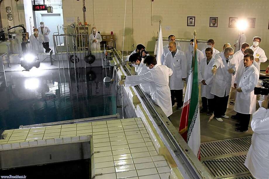 In this photo released by the Iranian President's Office, Iranian President Mahmoud Ahmadinejad, right is escorted by technicians during a tour of Tehran's research reactor centre in northern Tehran, Iran, Wednesday Feb. 15, 2012. In defiant swipes at its foes, Iran said Wednesday it is dramatically closer to mastering the production of nuclear fuel even as the U.S. weighs tougher pressures and Tehran's suspected shadow war with Israel brings probes far beyond the Middle East. Photo: -, Associated Press