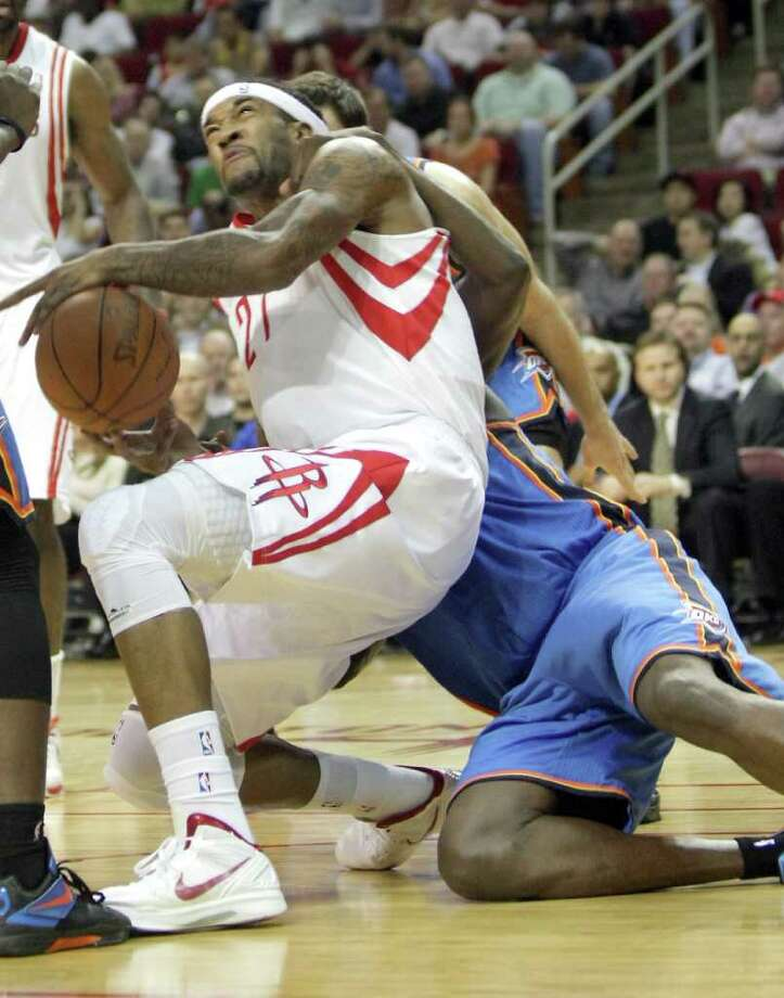 The Rockets came away with a hard-fought win Wednesday night, with Jordan Hill, left, paying the price for an encounter with Thunder center Nazr Mohammed in the fourth quarter. Photo: Nick De La Torre / © 2012  Houston Chronicle