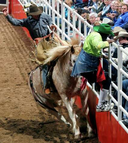 Rodeo clown Leon Coffee scrambles to get out of the way Tuesday night, Feb. 5, 2008 during the 6th night of the 59th Annual Stock Show & Rodeo at the AT&T Center in San Antonio as saddle bronc rider Ryan MacKenzie runs the arena fence. Photo: WILLIAM LUTHER, San Antonio Express-News File Photo / SAN ANTONIO EXPRESS-NEWS