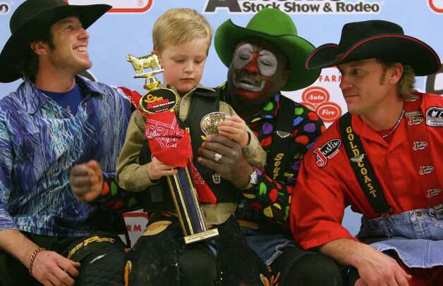 "Mac Northington, 5, (center) holds his trophy and beltbuckle while having his photo taken with bullfighters Seth Ryan ""Shorty"" Gorham, (from left) Leon Coffee and Darrell Dienfenbach after competing in the Mutton Bustin' event Sunday, Feb. 4, 2007 at the 58th Annual San Antonio Stock Show & Rodeo held the AT&T Center. Northington won the event with a score of 90. Photo: EDWARD A. ORNELAS, San Antonio Express-News File Photo / SAN ANTONIO EXPRESS-NEWS"