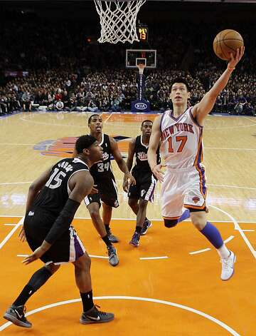 New York Knicks' Jeremy Lin (17) drives past Sacramento Kings' DeMarcus Cousins (15) during the second half of an NBA basketball game on Wednesday, Feb. 15, 2012, in New York. Lin had 10 points and 13 assists as the Knicks won the game 100-85. Photo: Frank Franklin II, Associated Press