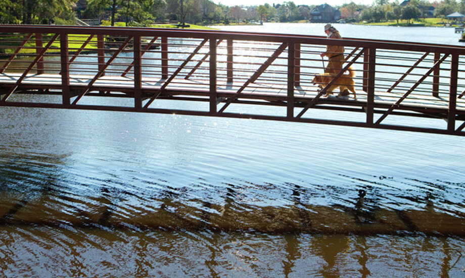 Harry Sharp walks his dog, Kelda, across a bridge that spans a portion of Lake Woodlands. (Brett Coomer  / Houston Chronicle)