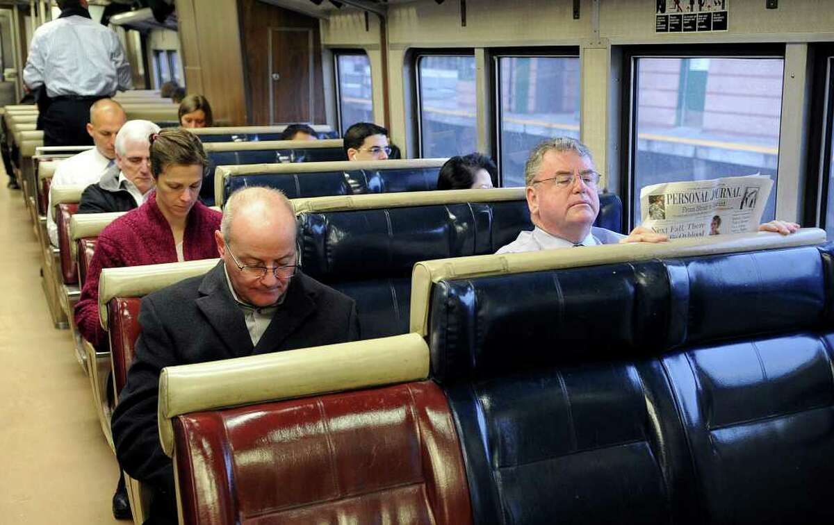 Commuters find seats, while avoiding the center seats in rows of three, during rush hour on a Metro-North train from Stamford to Grand Central Terminal on Thursday, February 16, 2012.