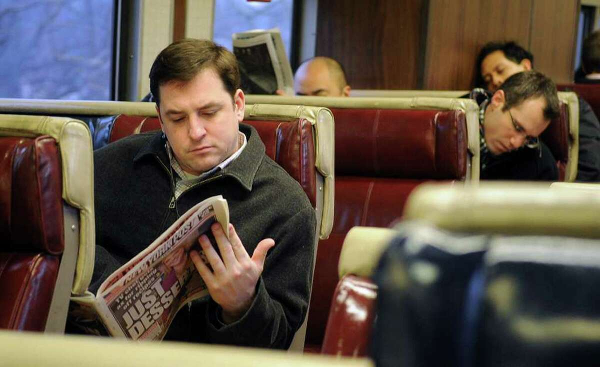 Mike Rogers reads a newspaper during rush hour on a Metro-North train from Stamford to Grand Central Terminal on Thursday, February 16, 2012.