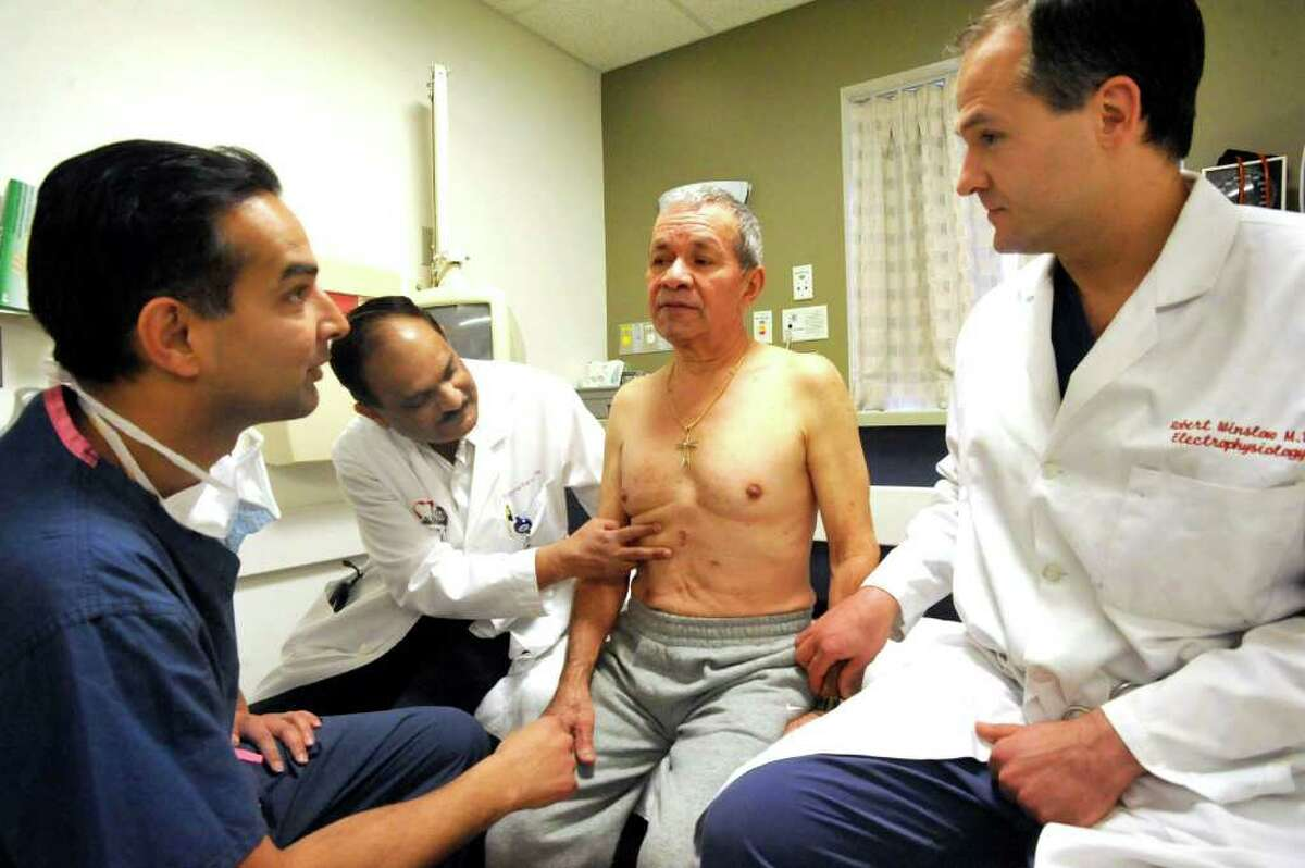 Dr. Muralie Chiravuri, an electrophysiologist, left, Dr. Eugene Fernandes, cardiothoracic surgeon, and Dr. Robert Winslow, directror of electrophysiology, right, examine Felix Rodriguez, Danbury Hospital's first patient to receive hybrid abalation, a minimally invasive surgical procedure to treat atrial fibrillation - an irregular, rapid heart rate that causes fatigue, shortness of breath and weakness. Photographed Thursday, Feb. 16, 2012.