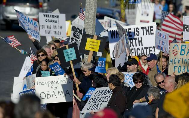 Signs being held by many people along Pacific Coast Highway in the Corona del Mar section of Newport Beach, Calif., early Thursday, Feb. 16, 2012, prior to the arrival of President Obama for a fundraiser at a private residence.  (AP Photo/The Orange County Register, Mark Rightmire)   MAGS OUT; LOS ANGELES TIMES OUT Photo: Mark Rightmire,, Associated Press