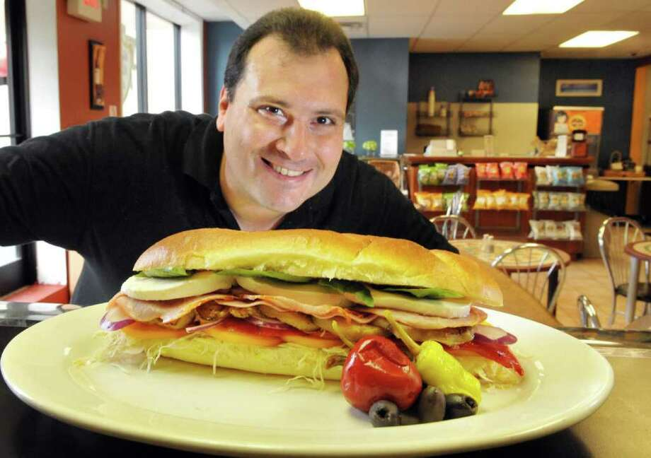 Crestwood Deli co-owner Danny Urschel shows off one of his Spaccanapoli sandwiches at the deli in Albany Wednesday Aug. 3, 2011.   (John Carl D'Annibale / Times Union) Photo: John Carl D'Annibale / 00014131A