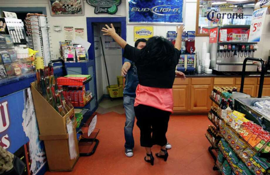 A female customer rushes into the Texas Food Mart on 446 Cupples Rd. and hugs owner Mamun Azam on Feb. 16, 2012.  Azam identified the woman as the person who bought the winning $22 million Lotto Texas ticket. Azam said he did not know the woman's name but said she regularly buys tickets from him that he thinks are for an office pool. Photo: William Luther, San Antonio Express-News / © 2012 SAN ANTONIO EXPRESS-NEWS