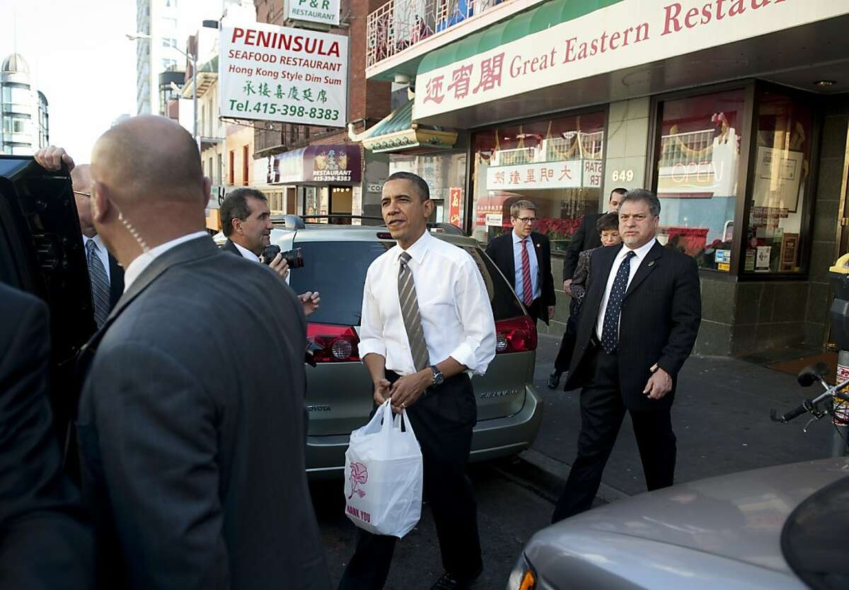 US President Barack Obama picks up a dim sum takeout lunch at the Great Eastern Restaurant in San Francisco's Chinatown on February 16, 2012. AFP PHOTO/Saul LOEB (Photo credit should read SAUL LOEB/AFP/Getty Images)