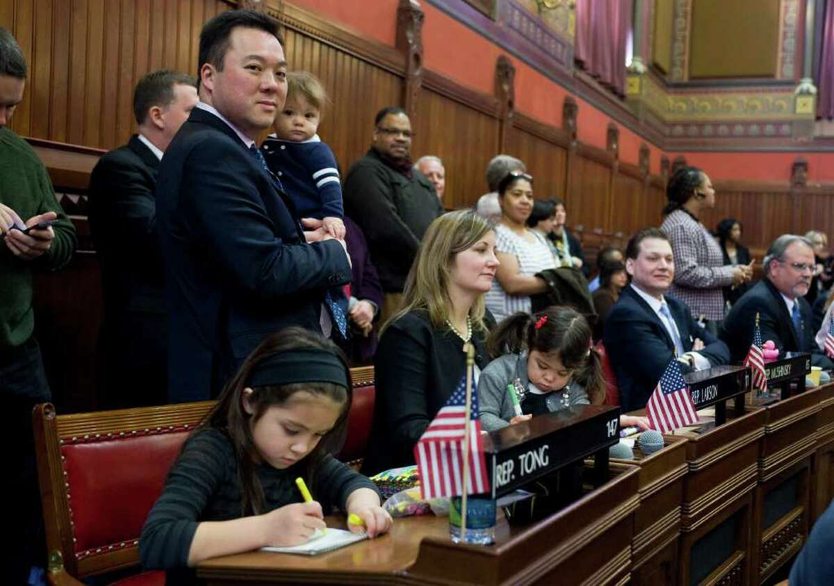 State Rep. William Tong, D-Stamford, left, holds his son Alexander with his family during the opening session at the State Capitol in Hartford Feb. 8. Tong is the only Asian-American running for the U.S. Senate this election season from the continental United States. (AP Photo/Jessica Hill)