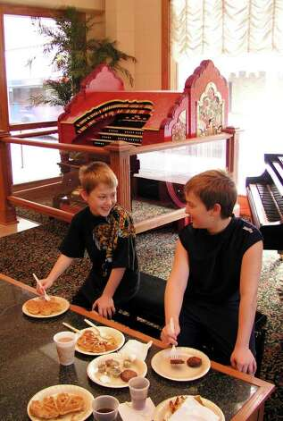 Jordan Hagerman, 8 (left), and his brother, James, 10, enjoy breakfast by an antique Wurlitzer theater organ in the lobby of the Drury Hotel River Walk on Friday, July 9, 2004. The organ will be moved to the rehabilitated Aztec Theatre when the renovation is completed. Photo: BILLY CALZADA, Express-News File Photo  / SAN ANTONIO EXPRESS-NEWS