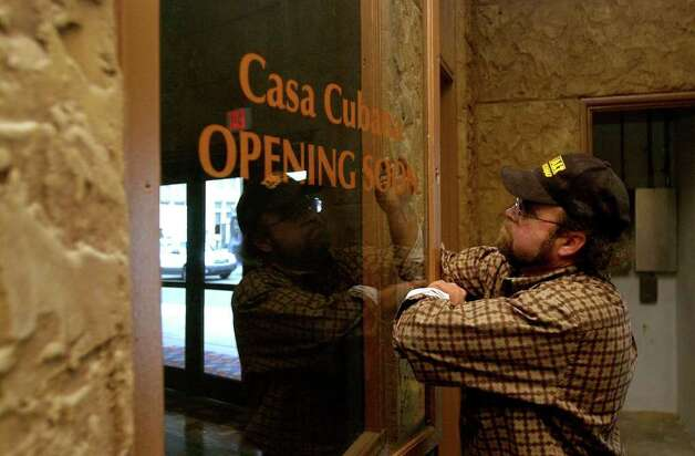 David Grojean straightens out a window decal at the historic Aztec Theatre on Friday, Feb. 24, 2006. The theater is scheduled to be reopened. The building, which was boarded up in 1989, was purchased by Euro Alamo Management in 1998. Renovations started in 2000. Photo: HELEN L. MONTOYA, Express-News File Photo  / © San Antonio Express-News