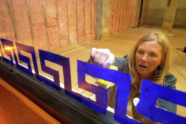 Anne Everett puts the finishing touches on the windows of the gift shop at the historic Aztec Theatre on Friday, Feb. 24, 2006. The theater is scheduled to be reopened. The building, which was boarded up in 1989, was purchased by Euro Alamo Management in 1998. Renovations started in 2000. Photo: HELEN L. MONTOYA, Express-News File Photo  / © San Antonio Express-News
