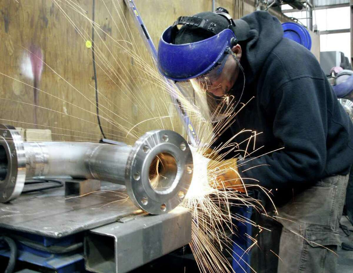 In this Feb. 13, 2012 photo, a workman cuts into a fitting at JV Northwest Monday, Feb.13, 2012, in Camby, Ore. The number of people seeking unemployment benefits fell to the lowest point in almost four years last week, the latest signal that the job market is steadily improving. (AP Photo/Rick Bowmer)