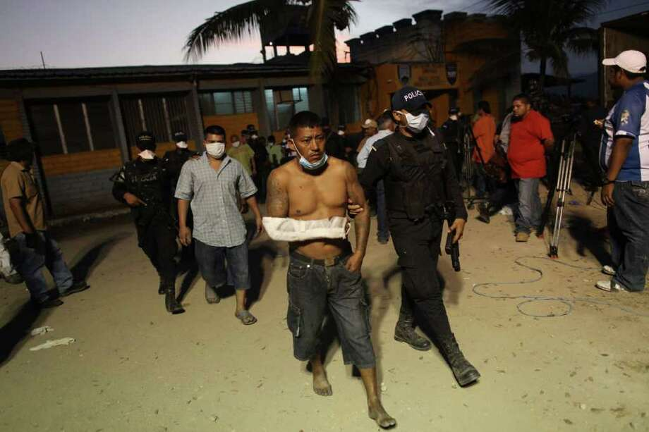 Police officers escort surviving inmates from the prison in Comayagua, Honduras, Wednesday Feb. 15, 2012. A fire started by a prisoner late Tuesday tore through the prison killing 358 inmates, said Supreme Court Justice Richard Ordonez, who is leading the investigation. Photo: Estbean Felix, Associated Press / AP
