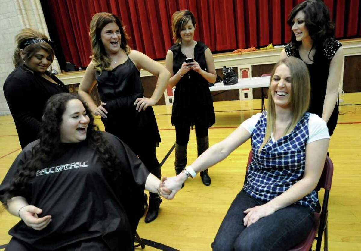 Law students Andrea Gellen, left, and Katherine Heeks, right, hold hands as they prepare to lose 10 inches of their long hair on Thursday, Feb. 16, 2012, at the Albany Law School in Albany, N.Y. Both women have donated their hair before. The professional legal fraternity Phi Alpha Delta, Rockefeller Chapter, sponsored the event and Rewind Salon of Rotterdam provided its services to benefit Locks of Love. (Cindy Schultz / Times Union)