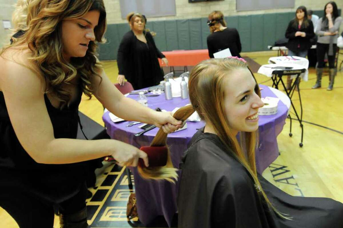 Albany College of Pharmacy student Natasha Vladick, right, prepares to lose 11 inches of her long hair as salon owner Lisa Lachanski brushes it out on Thursday, Feb. 16, 2012, at the Albany Law School in Albany, N.Y. Vladick said she donates her hair every two to three years. The professional legal fraternity Phi Alpha Delta, Rockefeller Chapter, sponsored the event and Rewind Salon of Rotterdam provided its services to benefit Locks of Love. (Cindy Schultz / Times Union)