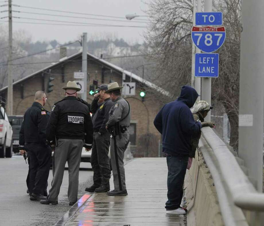 Law enforcement officials gather on the Green Island Bridge after a man jumped from the bridge in to the water below in Green Island, N.Y. Feb. 16, 2012.  The man was removed from the water and taken to Albany Medical Center by Watervliet Fire Department Ambulance.   ( Skip Dickstein / Times Union) Photo: Skip Dickstein / 2011
