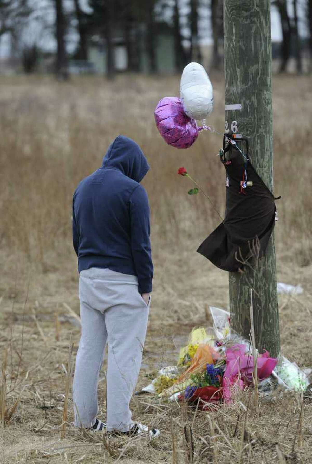 Trevonn Burns, a personal friend of the deceased stands by a makeshift memorial at the base of a utility pole near Johnson Road in Halfmoon, N.Y., the scene of a fatal accident Feb. 16, 2012 which took the life of Travis Taylor, 18, of Mechanicville who was driving a 2002 Chevrolet Cavalier at 9:18 p.m. last night when he lost control and the vehicle struck the telephone pole, police said. ( Skip Dickstein / Times Union)