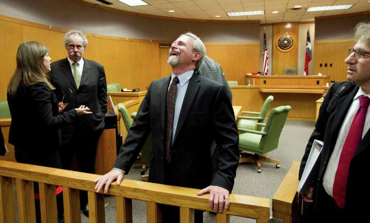 Michael Morton is all smiles after Judge Sid Harle ruled in favor of a court of inquiry for Judge Ken Anderson. At right is Morton's attorney, Barry Scheck. Second from left is Bill Allison, Morton's original lawyer.