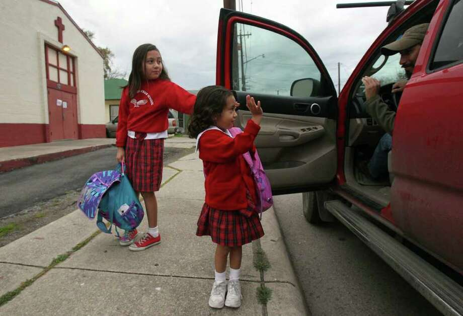 Marcus Rodriguez (right) drops off his daughters Aurelia Rodriguez, 9, (left) and Eva Rodriguez, 4, at St. Philip of Jesus School Thursday February 16, 2012. Two historic Catholic schools on the South Side will close at the end of the school year in a consolidation plan that aims to replace them with a regional academy next to Mission Concepci—n. The two schools that will close are St. Cecilia and St. Philip of Jesus. Photo: JOHN DAVENPORT, SAN ANTONIO EXPRESS-NEWS / SAN ANTONIO EXPRESS-NEWS (Photo can be sold to the public)