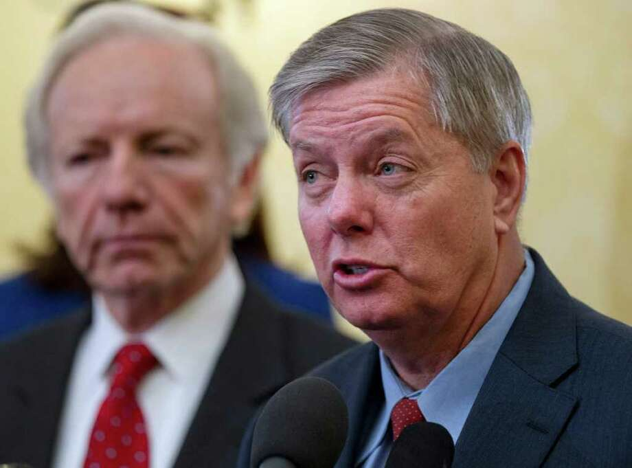 Sen. Lindsey Graham, R-S.C., right, accompanied by Sen. Joseph I. Lieberman, I-Conn., lead a bi-partisan group of senators in supporting President Obama's sanctions against Iran for pursuing nuclear weapons, Thursday, Feb. 16, 2012, during a news conference on Capitol Hill in Washington.  (AP Photo/J. Scott Applewhite) Photo: J. Scott Applewhite