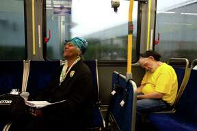 """While looking at her daily planner, Janis Scott, 60, smiled saying """"I have so many events scheduled I have to make sure I know what I'm doing,"""" she said as she rode the Metro Route 30 bus next to fellow rider, Walter Simpson, right, while on the way to a museum exhibit at Texas Southern University. Scott, who is retired, is known by many as """"The Bus Lady,"""" because she uses public transportation from her home near the ship channel on Houston's east side and to travel to free events from morning until night almost daily."""
