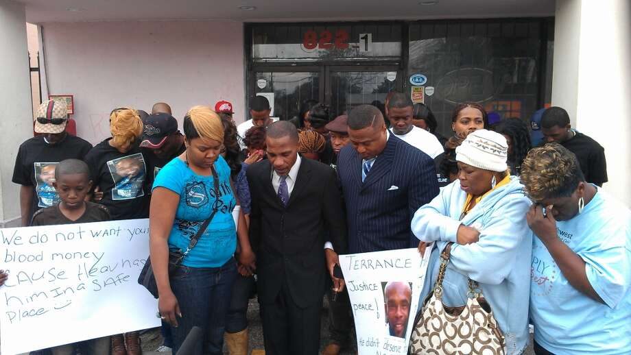 With community activist  Quanell X, protesters gather on Thursday at a store on West Little York where Terrance Hall, 33, was killed.