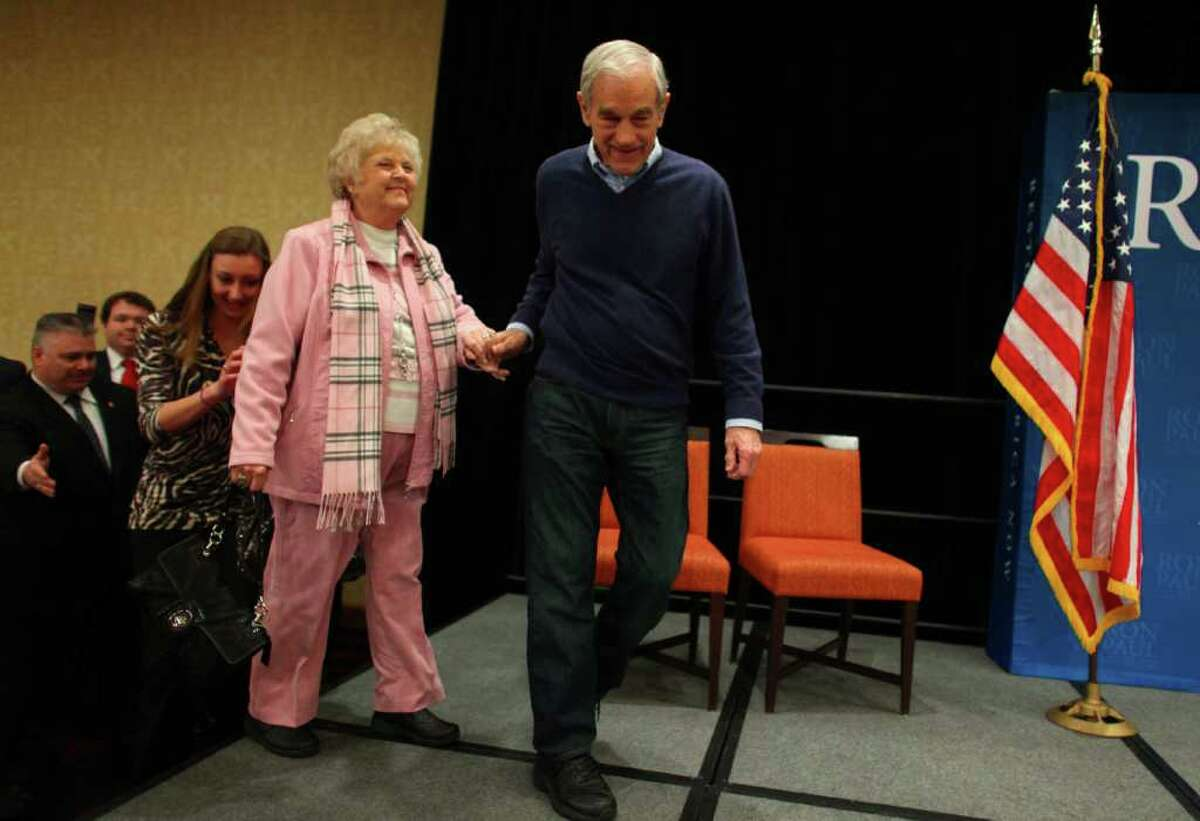 Republican presidential candidate Ron Paul takes the stage with his wife Carol Wells at the SeaTac Double Tree hotel on Thursday February 16, 2012 during an energetic campaign rally. An overflow crowd turned out for the candidate.