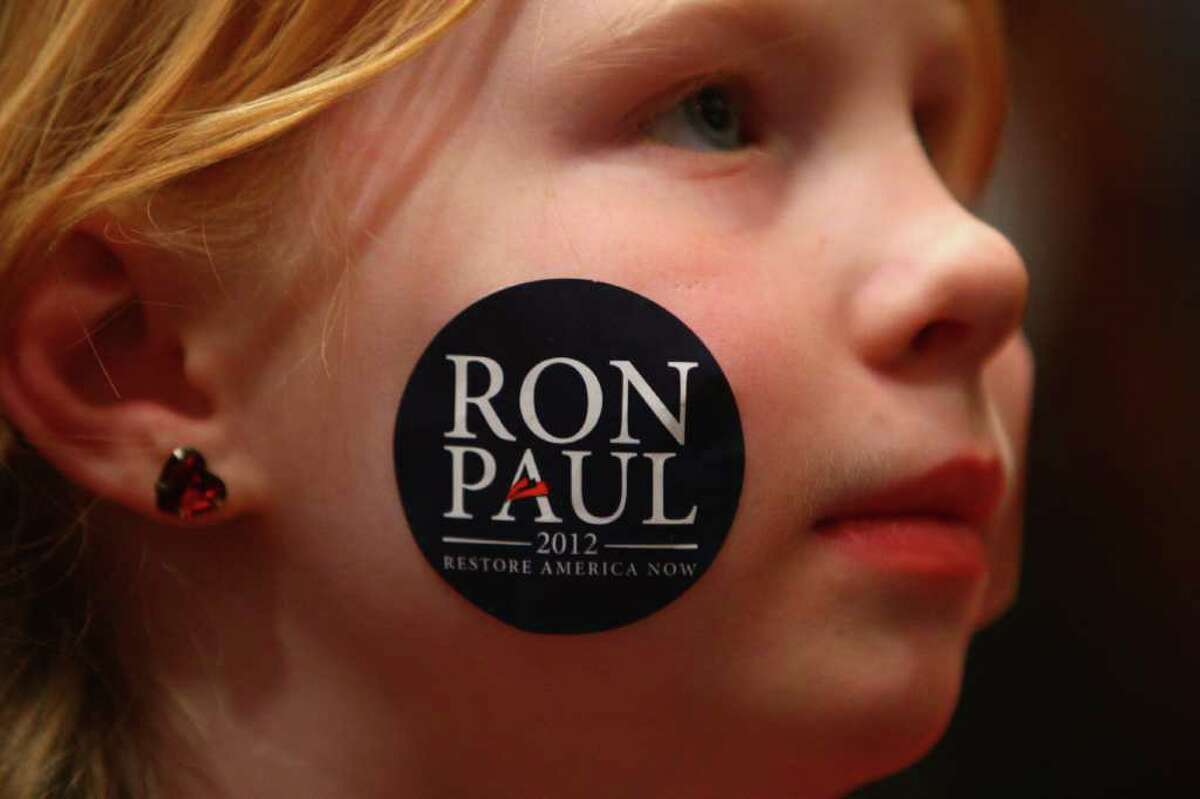 A young girl shows her support for Republican presidential candidate Ron Paul at the SeaTac Double Tree hotel on Thursday February 16, 2012 during an energetic campaign rally. An overflow crowd turned out for the candidate.