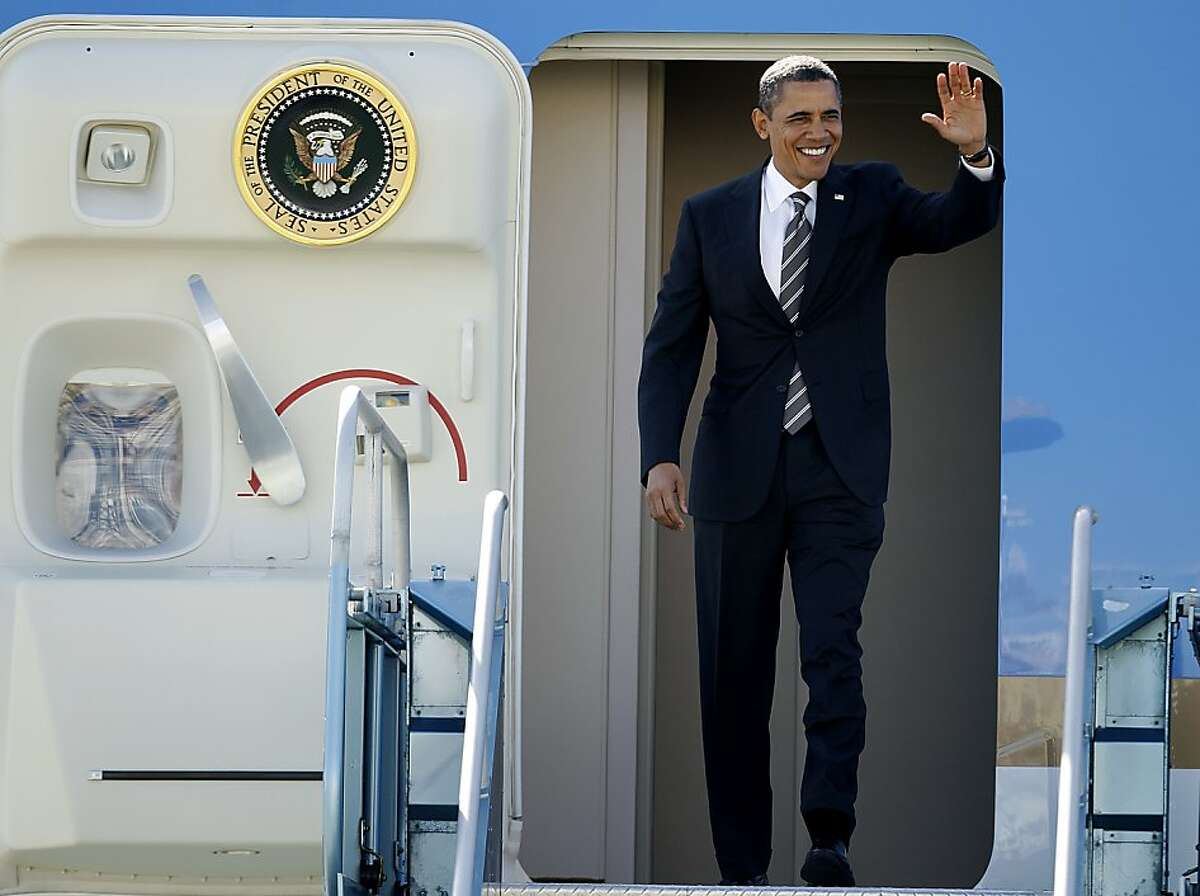 President Barack Obama waves as he emerges from Air Force One after arriving at SFO in San Francisco, Calif. on Thursday, Feb. 16, 2012 to attend private fundraising events this evening.
