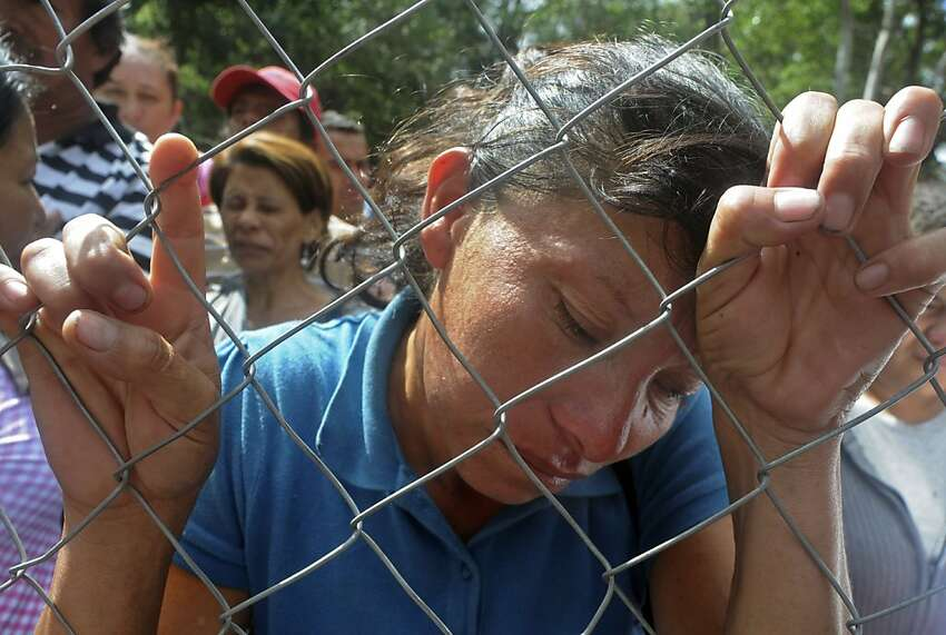 Maria Hernandez stands behind a fence as she waits for information about her relative outside the morgue in Tegucigalpa, Honduras, Thursday Feb. 16, 2012. Relatives have arrived at the morgue from the city of Comayagua, where a fire broke out on Tuesday night at the city's prison, killing over 300 inmates.