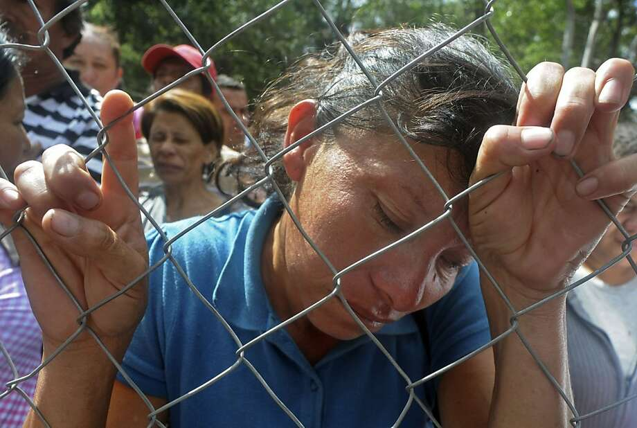 Maria Hernandez stands behind a fence as she waits for information about her relative outside the morgue in Tegucigalpa, Honduras, Thursday Feb. 16, 2012.  Relatives have arrived at the morgue from the city of Comayagua, where a fire broke out on Tuesday night at the city's prison, killing over 300 inmates. Photo: Fernando Antonio, Associated Press