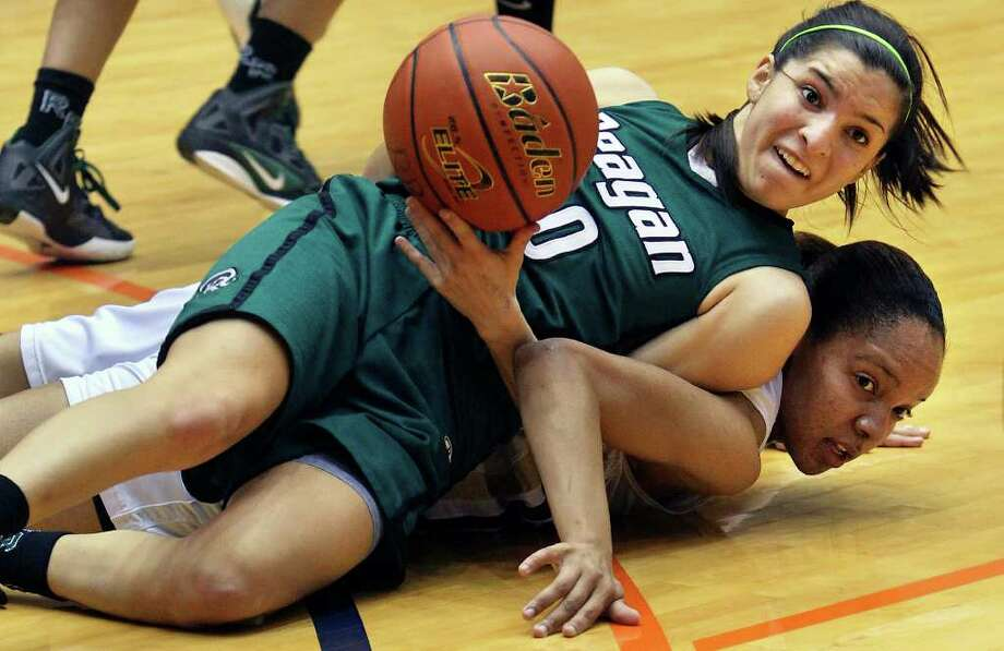 Reagan point guard Tessa Ramirez passes the ball away after winning a scramble on the floor against O'Connor Ebony Easter as the Rattler girls defeat Panthers 45-42 in playoff action at the UTSA Convocation Center on Thursday, Feb. 16, 2012. Photo: TOM REEL, San Antonio Express-News / San Antonio Express-News