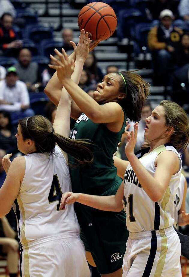 Reagan guard Sabrina Perry lofts a shot over O'Connor's Kristina Schuler (4) and Shelbi Miller as the Rattler girls play the Panthers in playoff action at the UTSA Convocation Center on Thursday, Feb. 16, 2012. Photo: TOM REEL, San Antonio Express-News / San Antonio Express-News
