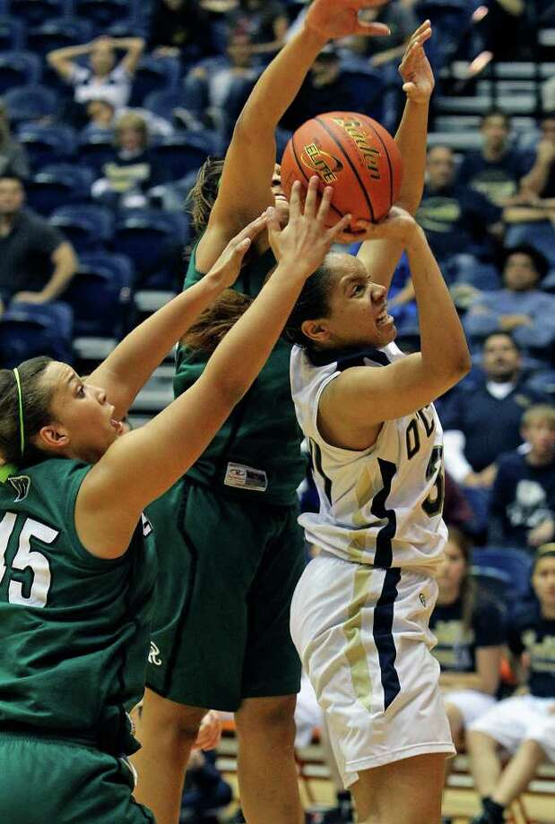 O'Connor forward Ebony Easter tries to squeeze off a shot through the defense of Reagan's Corrigan Tibbs (45) and Sabrina Berry as the Rattler girls play the Panthers in playoff action at the UTSA Convocation Center on Thursday, Feb. 16, 2012. Photo: TOM REEL, San Antonio Express-News / San Antonio Express-News