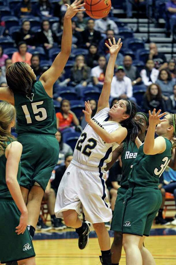 Reagan's Sabrina Berry blocks a running shot by O'Connor's Amber Vidal as the Rattler girls play the Panthers in playoff action at the UTSA Convocation Center on Thursday, Feb. 16, 2012. Photo: TOM REEL, San Antonio Express-News / San Antonio Express-News