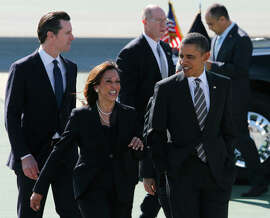 President Obama walks with state Attorney General Kamala Harris and Lt. Gov. Gavin Newsom after his arrival aboard Air Force One at SFO in February 2012.