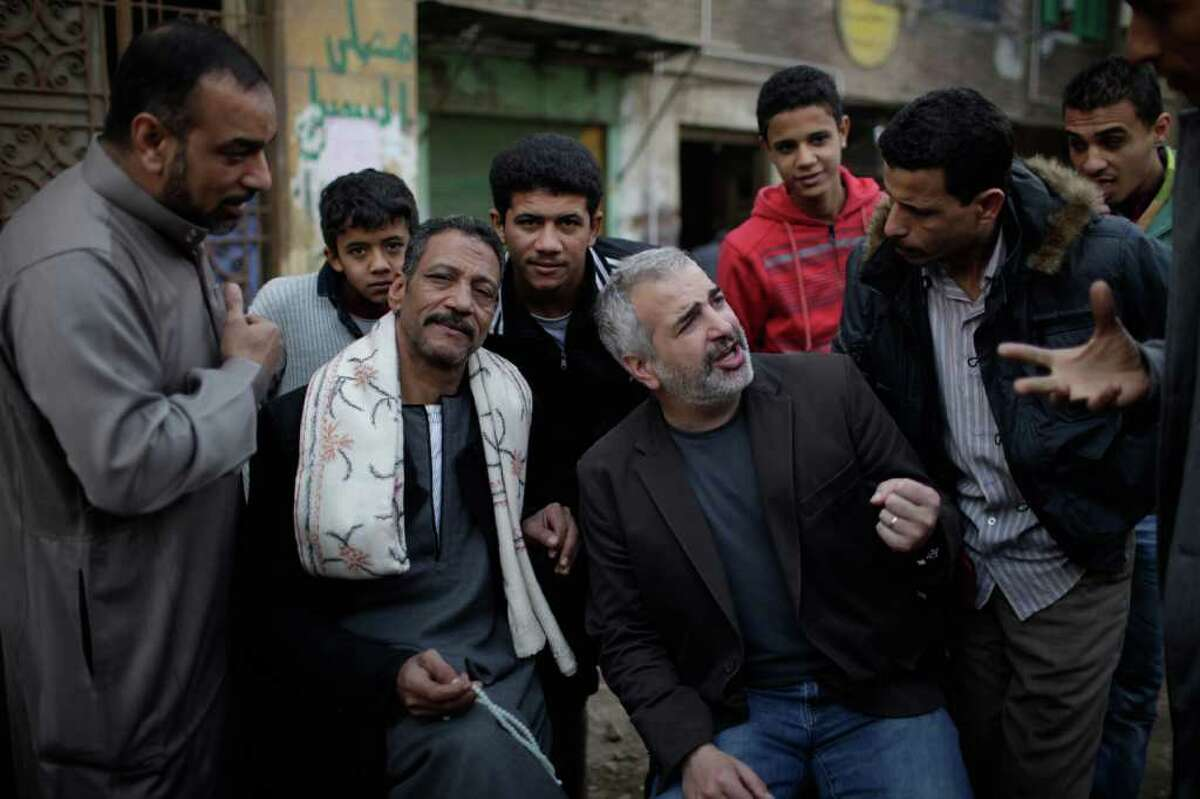 In this Feb. 2, 2011 photo provided by The New York Times, Times journalist Anthony Shadid, middle right, interviews residents of Embaba, a lower class Cairo neighborhood, during the Egyptian revolution. The New York Times said Shadid died Thursday, Feb. 16, 2012, apparently of an asthma attack, while on assignment in Syria. He was 43. (AP Photo/Ed Ou for The New York Times) MANDATORY CREDIT: ED OU FOR THE NEW YORK TIMES, VIA THE ASSOCIATED PRESS