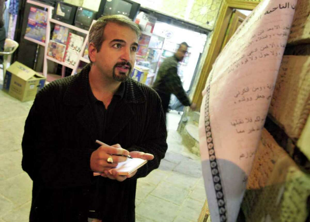 Anthony Shadid takes notes outside Ayatollah Sistani's office in Najaf Dec. 3, 2003. The city of Najef, south of Baghdad, is the site of one of the holiest mosques' in Shiite religious beliefs. Shadid, a two-time Pulitzer Prize winner who strove to capture untold stories in Middle East conflicts from Libya to Iraq, died Thursday Feb. 16, 2012 in eastern Syria after slipping into the country to report on the uprising against its president. (AP Photo/Bill O'Leary, The Washington Post)