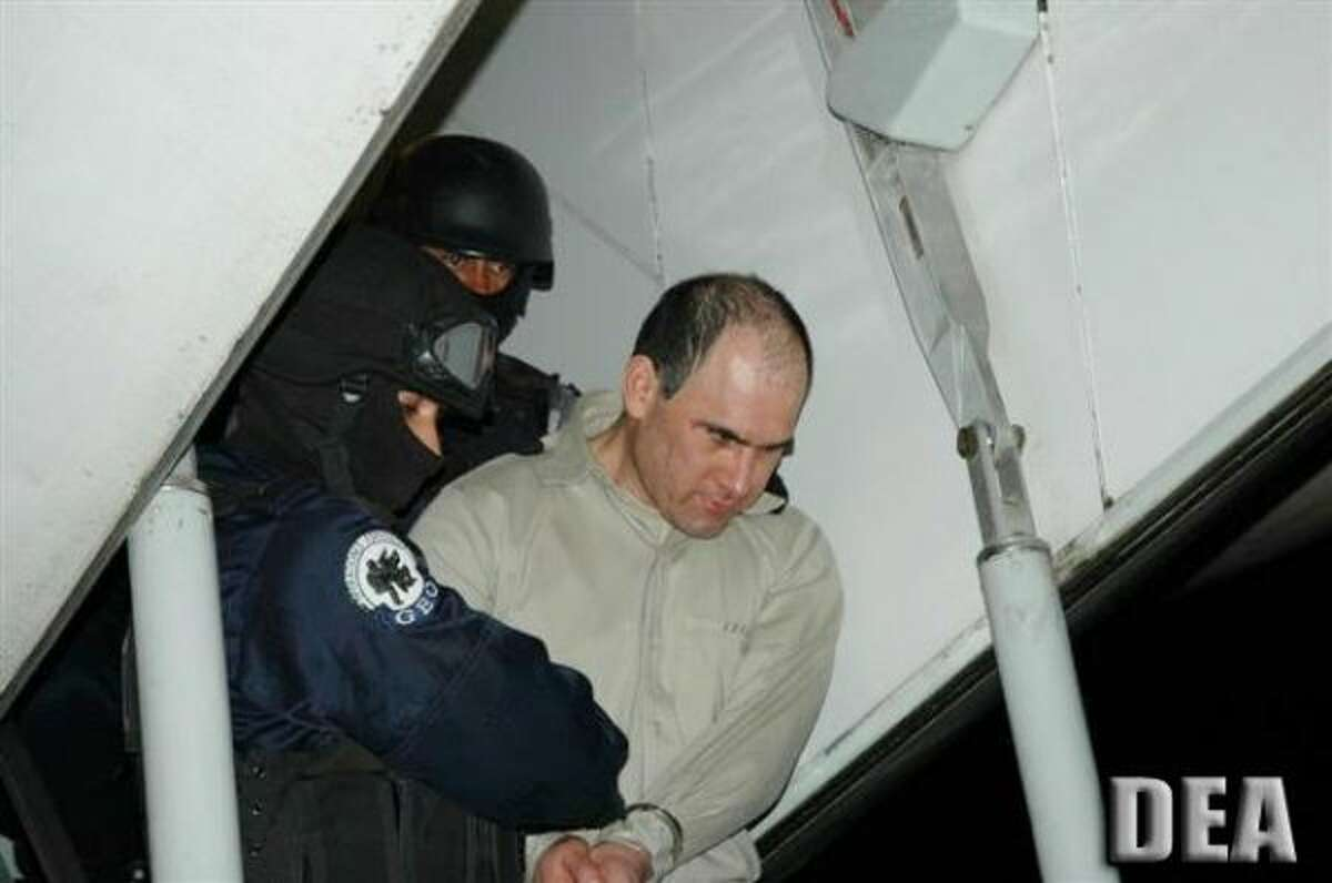 Osiel Cardenas Guillen, who was formerly the reputed principle leader of the Gulf Cartel is escorted by U.S. federal agents in January 2007, moments after stepping after a Mexican government plane that flew him to Houston to face criminal charges. (DEA)