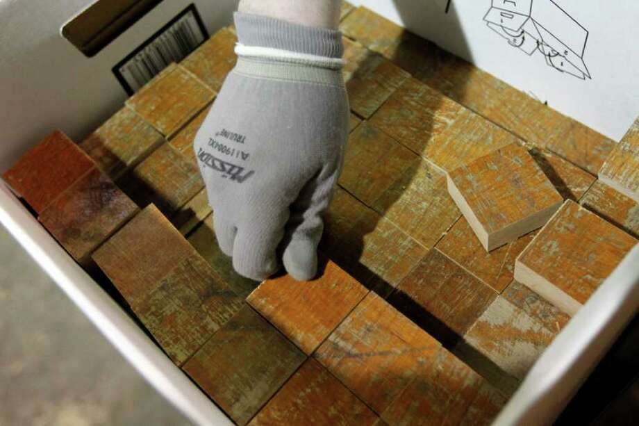 An employee at EBS Millwork Inc., places cut sections of the court in which Wilt Chamberlain scored 100 points on March 2, 1962, in a box. The 76ers will mark the 50th anniversary of the NBA record by giving pieces to fans. Photo: AP