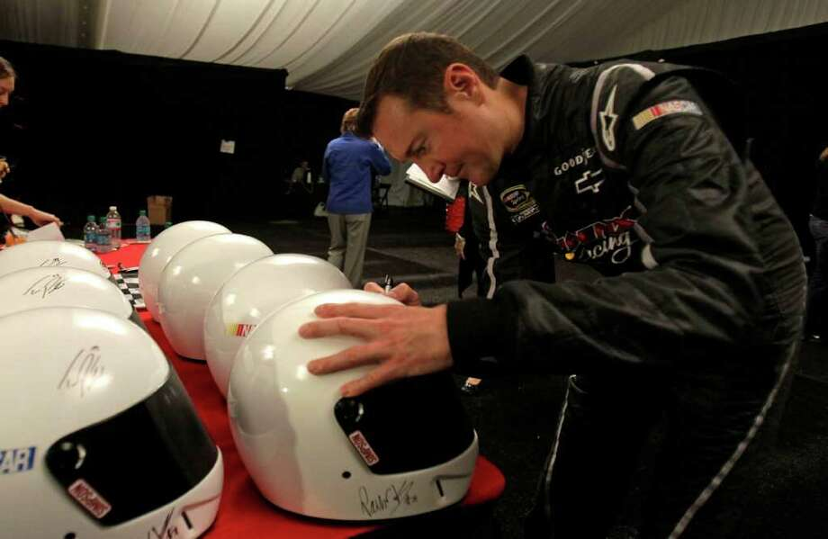 Kurt Busch, autographing helmets during NASCAR media day, was the 2004 NASCAR champ but is now driving for the underfunded Phoenix Racing. Photo: AP
