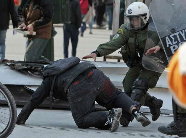 Riot police catch a high school student during an anti-austerity protest in Athens. Tensions between Athens and other European capitals hit new highs this week as eurozone ministers delayed to next Monday a decision on a bailout agreement and demanded more commitments from Greece. (AP Photo/Thanassis Stavrakis) Photo: Thanassis Stavrakis, Associated Press / AP2012